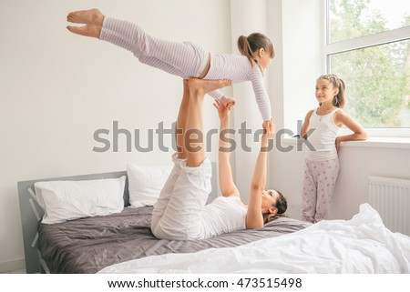 Young mother with children gets up and doing morning yoga exercises in bed. Healthy lifestyle concept