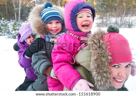 Young mother with  children playing on snow in winter time - stock photo