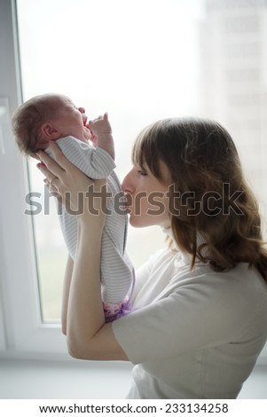 young mother with crying baby - stock photo