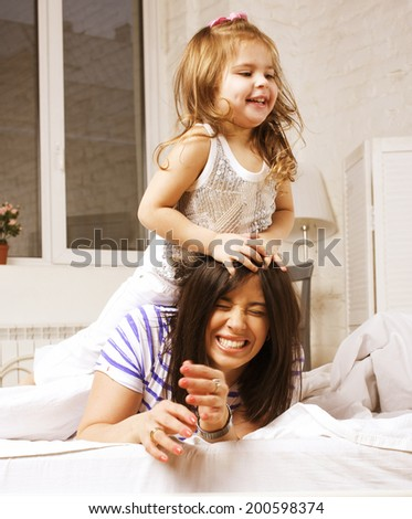 young mother with daughter at home playing, happy family - stock photo