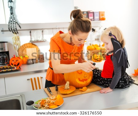 Young mother with daughter in bat costume carving big orange pumpkin Jack-O-Lantern for Halloween party in decorated kitchen. Traditional autumn holiday - stock photo