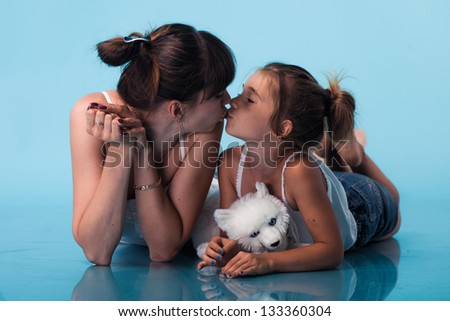 Young mother with daughter on blue background