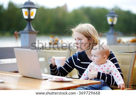 Young mother with her adorable baby girl working or studying on laptop in outdoor cafe  - stock photo