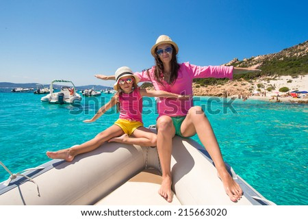 Young mother with her adorable daughter enjoy vacation on a boat - stock photo