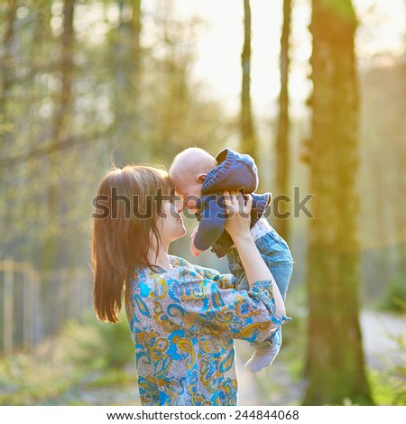 Young mother with her adorable little baby in forest on a spring day - stock photo