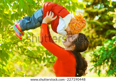 Young mother with her baby in autumn park - stock photo
