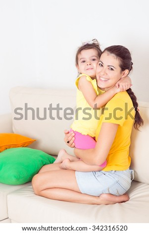 young mother with her baby on the couch - stock photo