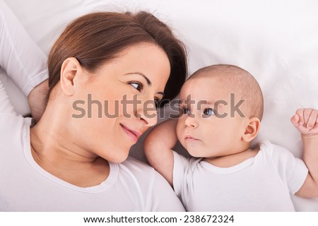 Young mother with her baby relaxing on bed - stock photo