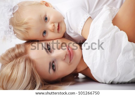 Young mother with her baby studio shot - stock photo