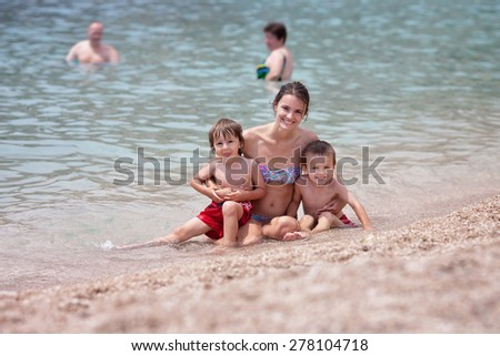 Young mother with her children on the beach, having fun