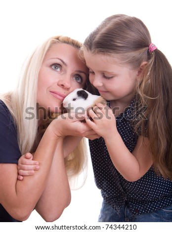 Young mother with her daughter holding a guinea pig - stock photo