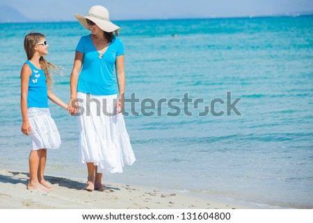 Young mother with her daughter walking on tropical beach - stock photo
