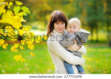 Young mother with her little baby boy in the autumn park  - stock photo