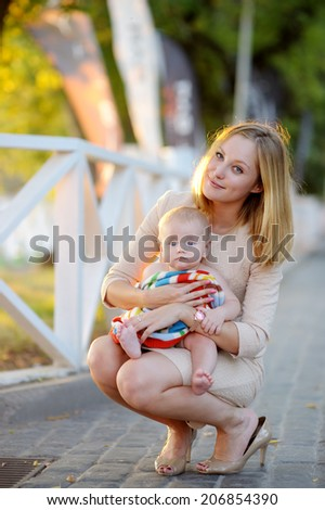 Young mother with her little baby outdoors - stock photo