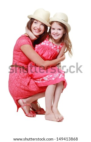 Young mother with her little daughter in pink dresses and hats - stock photo