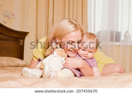 Young mother with her little daughter playing on the bed at home