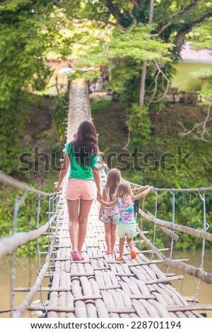 Young mother with her little girls on suspension bridge over the River - stock photo