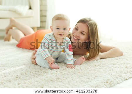 Young mother with her little son play at home