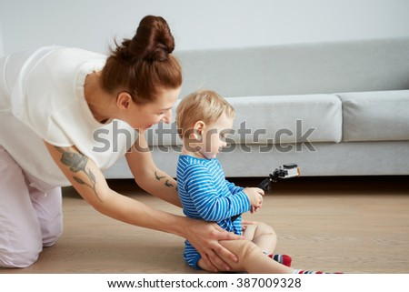 Young mother with her one years old little son dressed in pajamas are posing. Mom with son taking selfie on her smartphone or action camera in the bedroom.  Selective focus. Casual lifestyle photo. - stock photo