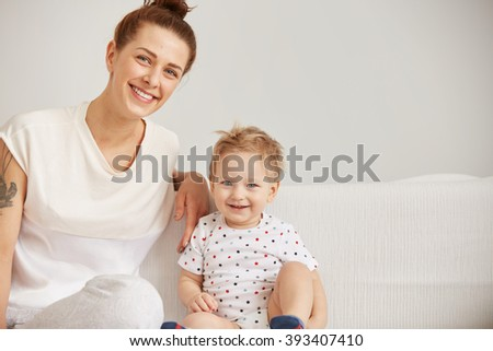Young mother with her one years old little son dressed in pajamas are relaxing and playing in the bed at the weekend together, lazy morning, warm and cozy scene. Selective focus