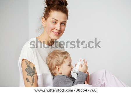 Young mother with her one years old little son dressed in pajamas  gives to drink water from cup in the bedroom at the weekend together, lazy morning, warm and cozy scene. Selective focus.