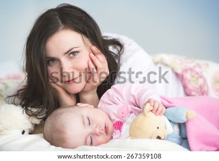 Young mother with her sleeping  baby  in bed - stock photo