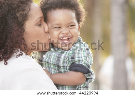 Young mother with her smiling toddler in her arms - stock photo