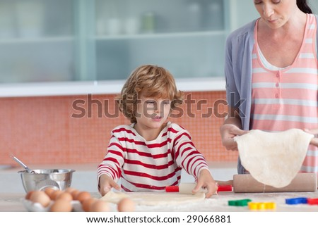 Young Mother with her son Baking in the Kitchen