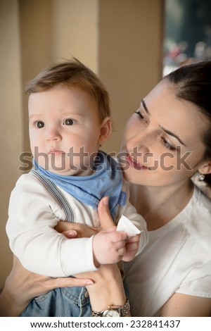 Young mother with her son in her arms.Portrait of a happy mother and baby laughing. Young mother holding her baby