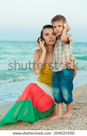 Young mother with her son on the beach with shells. Listening to the sea. - stock photo