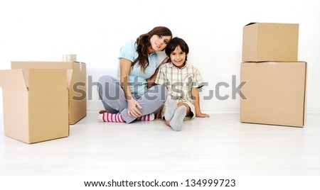 Young mother with her son packing card boxes and moving to new home
