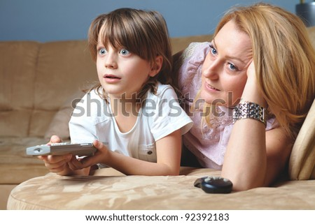 Young mother with her son watch tv, happy and surprised by something - stock photo