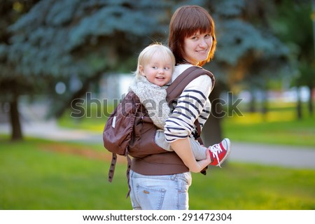 Young mother with her toddler child in a baby carrier - stock photo