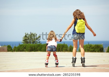 Young mother with her 5 years old daughter rollerskating in park, rear view - stock photo