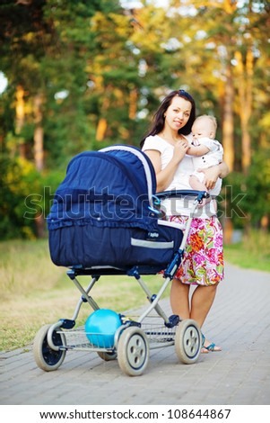 young mother with infant baby and carriage outdoors