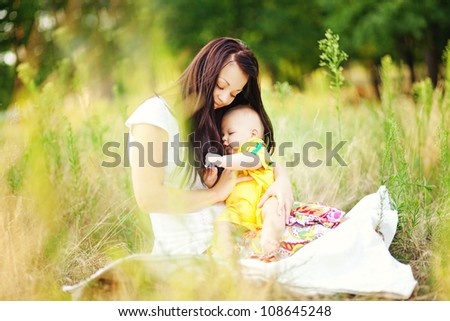 young mother with infant baby outdoors - stock photo