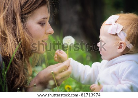 Young mother with little baby at the park - stock photo