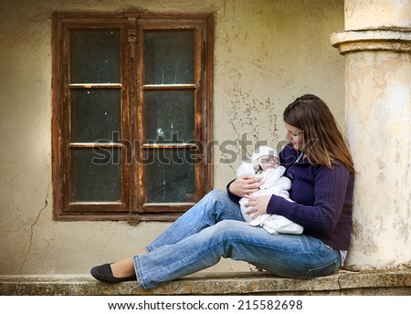 Young mother with little baby boy outside the old house - stock photo