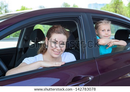 Young mother with little child sitting in land vehicle. Caucasian two people family - stock photo