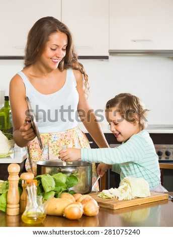 Young mother with little daughter cooking soup at home kitchen