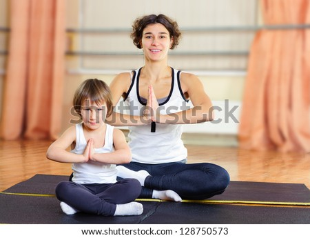 Young mother with little daughter exercising in gym