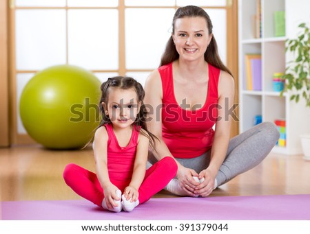 Young mother with little daughter exercising in gym at home - stock photo