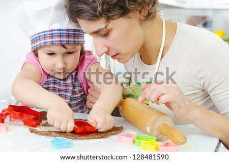 Young mother with little daughter shaping cookies - stock photo
