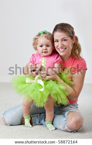 Young mother with one year old daughter - stock photo