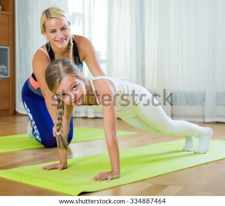 Young mother with small daughter working out and smiling