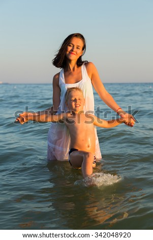 Young mother with son playing in the sea. A beautiful young mother and little boy happy gaming in water. Family holidays at sea. Photo for family and social magazines, posters and websites. - stock photo