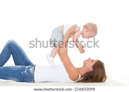 Young mother with sweet child play on a white background. Happy family. - stock photo
