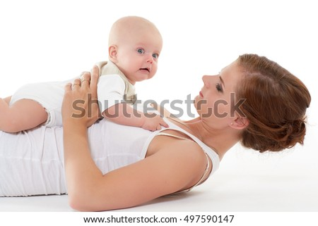 Young mother with sweet child play on a white background. Happy family. Six month.