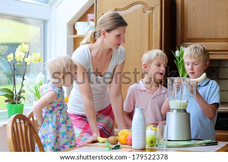 Young mother with three kids, teenager twin sons and little toddler daughter, standing together on sunny kitchen preparing healthy drink with milk and fruits. Boy is placing banana in the mixer.