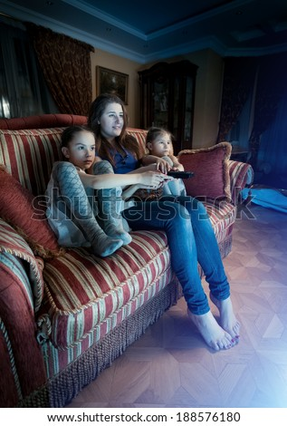 Young mother with two daughters watching horror movie at night - stock photo